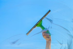 Window cleaner using a squeegee to clear suds from a window