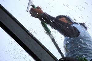 Window cleaner hosing down a pane of glass