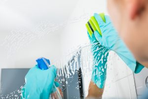Cleaner in rubber gloves spraying and wiping down a mirror