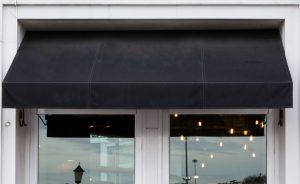 A black awning over an upmarket retail establishment