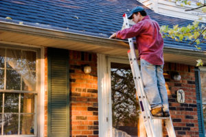 a cleaner on a ladder removing detritus from a home's gutter