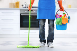 a uniformed cleaner with a mop and cleaning materials, cleaning a kitchen