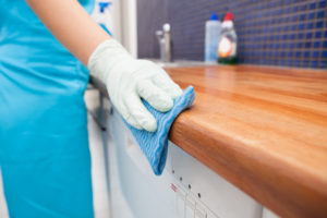 a uniformed cleaner wiping down a kitchen surface