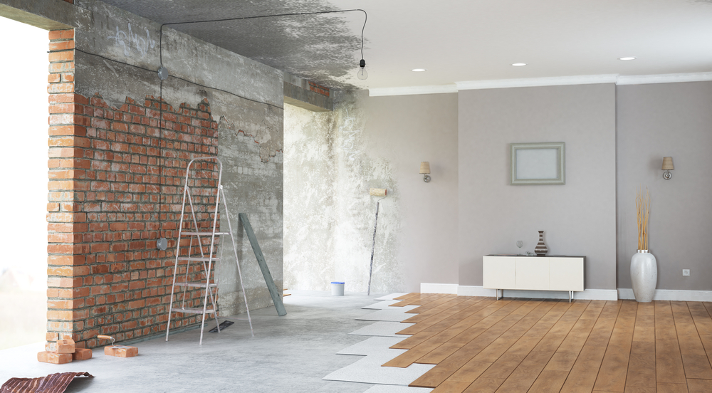 a luxurious looking room that is halfway through renovation, with exposed brick wall, ceiling, and floor.