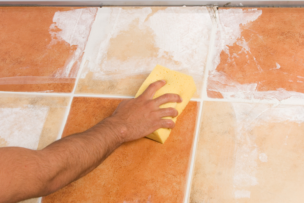 someone using a sponge to clean tiles and grout