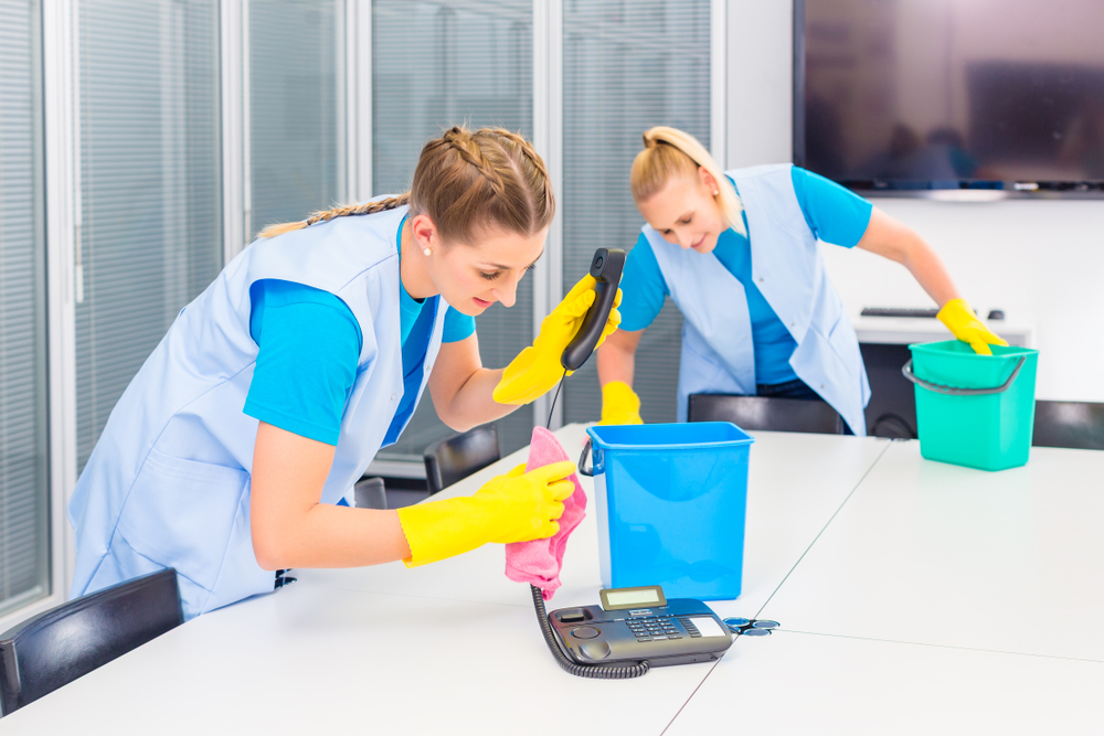 two uniformed cleaning staff working on a table surface