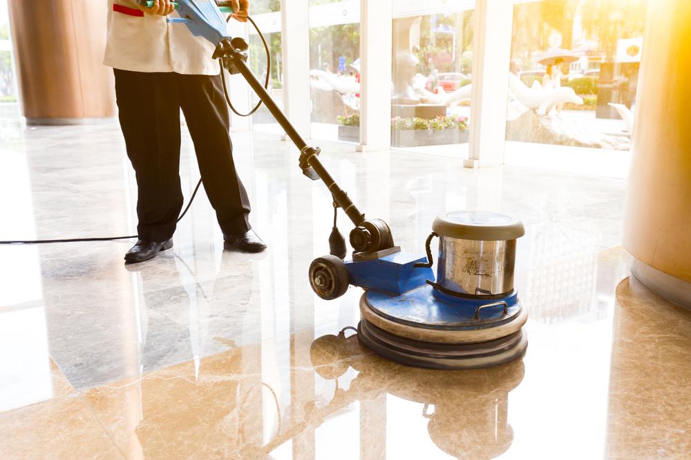 a cleaner uses a floor buffer