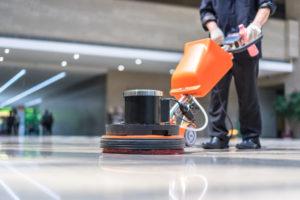 a uniformed worker uses a floor buffer in a lobby