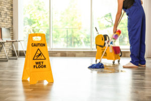 a uniformer cleaner uses a cleaning trolley on a hard floor