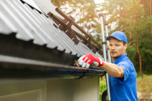 a professional on a ladder cleaning leaf matter out of a home's gutter