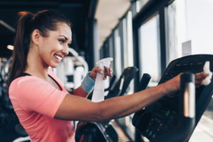 a smiling woman cleans a gym machine