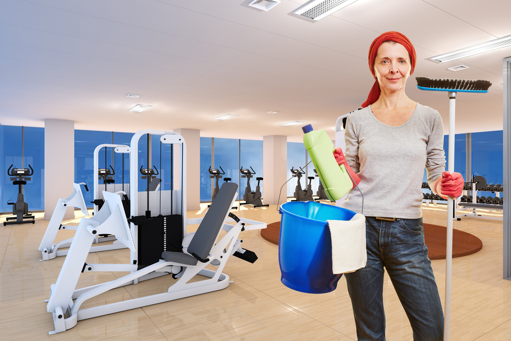 a cleaner with cleaning equipment standing in front of a clean gym