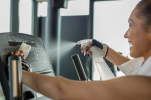 a uniformed cleaner sprays and cleans a gym machine