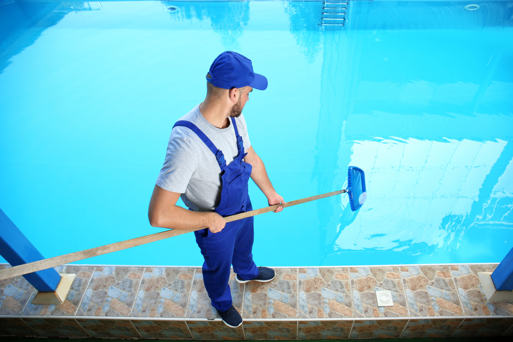 a uniformed cleaner uses a tool to clean a swimming pool