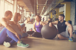 friends in workout gear sit and chat in a clean gym