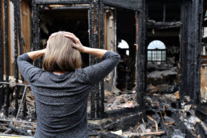 a woman aghast at her burned out home